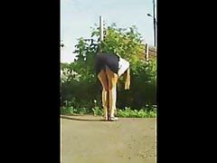 Attraktiva flicka böjer sig rätt över i en minikjol